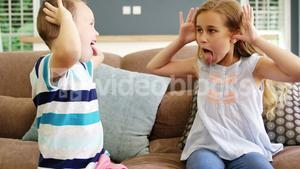 Boy and girl sitting on sofa teasing each other