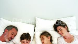 Family sleeping in bedroom