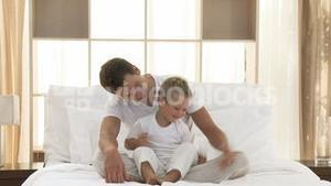 Father and son playing in bed