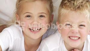 Close up of smiling siblings in bed
