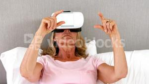 Senior woman using virtual reality headset on bed in bedroom