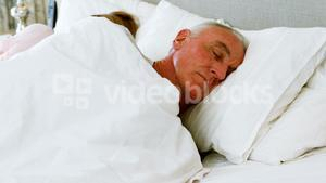 Senior man sleeping besides woman on bed