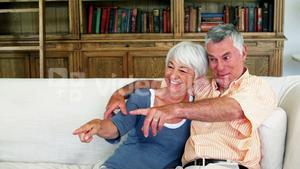 Senior couple sitting together on sofa and watching tv
