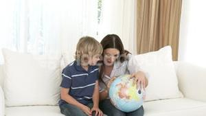 Mother and son examining a terrestrial globe