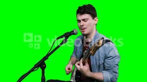 Male musician singing while playing guitar