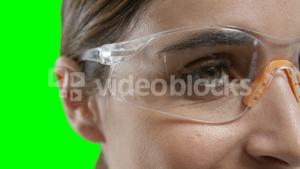 Woman wearing futuristic goggles against green screen