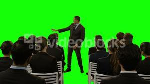 Businessman using futuristic digital screen while giving presentation to colleagues