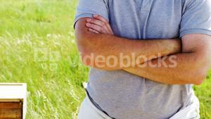 Confident beekeeper standing with arms crossed