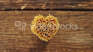 Bunch of spaghetti arranged in heart shape on a wooden table