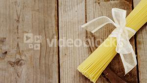 Bunch of raw spaghetti tied up with white ribbon