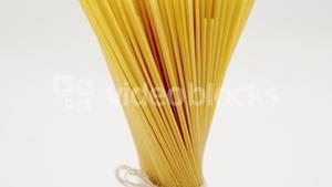 Bunch of raw spaghetti tied up with rope vertically