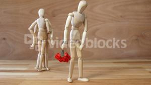 Figurine with bunch of roses jealous with other couple on wooden background