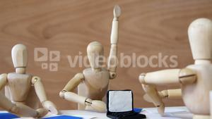 Wooden figurines having meeting in conference room in office on wooden background