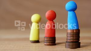 Group of red, blue and yellow figurines standing on piles of coins