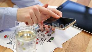 Businesswoman using mobile phone at desk with graph chart and digital tablet on table