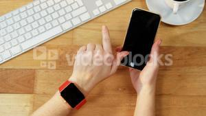 Hand of businesswoman using mobile phone at desk