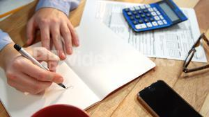 Hand of businesswoman writing on book at desk