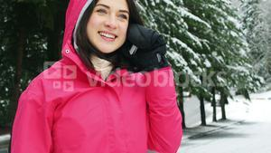 Smiling woman in warm clothing talking on mobile phone