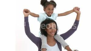Ethnic mother giving her daughter piggyback ride