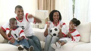 Family watching a football match at home