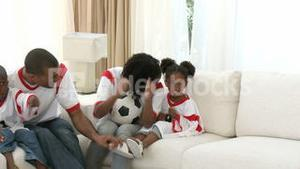 AfroAmerican family watching a football match at home