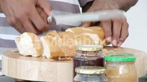 Close up of people cutting bread in the kitchen