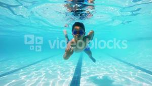 Boy swimming underwater in pool