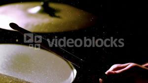 Drummer playing at the drums with drum stick