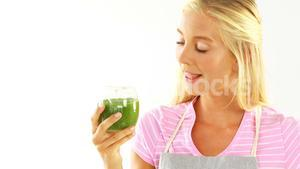 Smiling woman drinking vegetable smoothie against white background