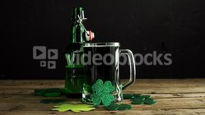 Green beer, bottle and shamrocks on wooden table for st patricks