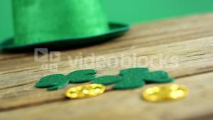 Leprechauns hat and hat and shamrocks on wooden table for st patrick