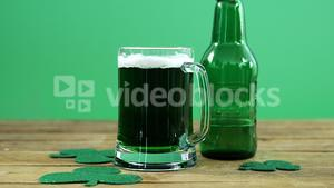 Green pint of beer and bottle on table for st patrick