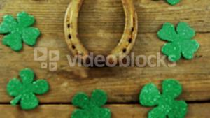 Horse shoe  surrounded by shamrocks on wooden table for st patricks