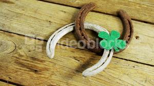 Horse shoes and shamrock side view on wooden table for st patricks
