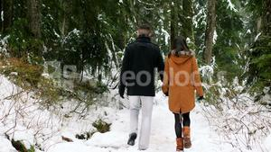 Couple walking on the snow covered path in the forest