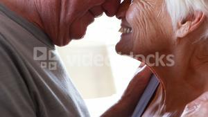 Happy senior couple romancing in bedroom