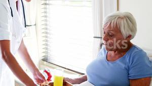 Female doctor serving breakfast to senior woman in the bedroom