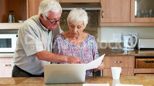 Senior couple calculating their bills on laptop in the kitchen