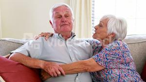 Senior couple interacting with each other in living room