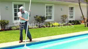 Senior man cleaning swimming pool with net