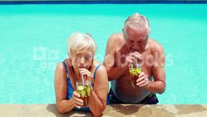 Senior couple interacting with each other while having glasses of iced tea