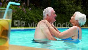 Senior couple kissing each other in the pool