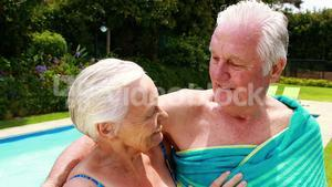 Senior couple kissing each other in the poolside