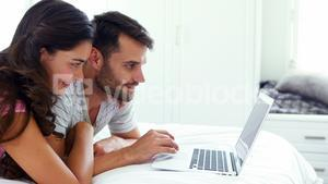 Couple interacting with each other while using laptop on bed