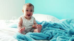 Playful baby girl sitting on bed