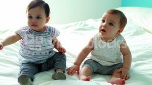 Two cute baby girls sitting on bed