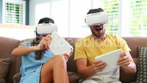 Couple using virtual reality headset in living room