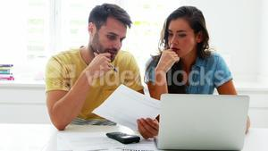 Worried couple calculating their bills with laptop in the kitchen
