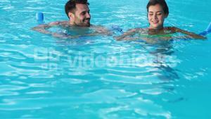 Smiling couple swimming with inflatable tubes