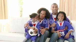 Excited AfroAmerican family watching a football match